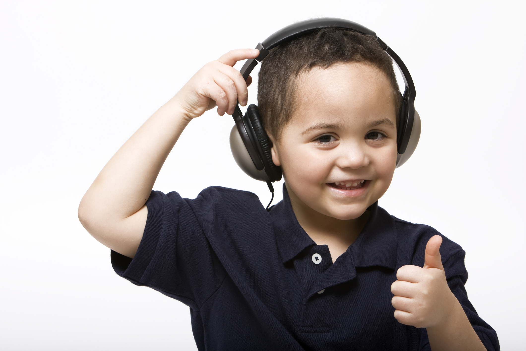 Young boy removing headphones giving thumbs up sign